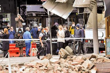 People survey the damage caused to a building in the popular shopping Chapel Street in Melbourne after Wednesday's earthquake.