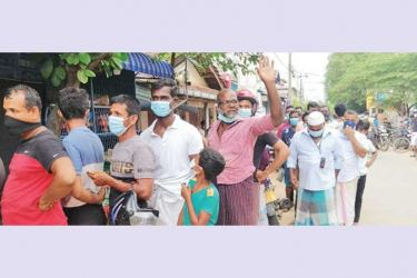 Residents of Batticaloa waiting in a queue to buy confiscated packets of milk powder from the CAA Officials.