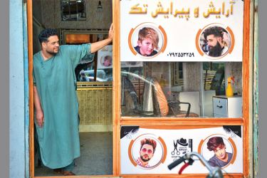 A barber waits for customers at his shop in Herat, Afghanistan on September 19, 2021