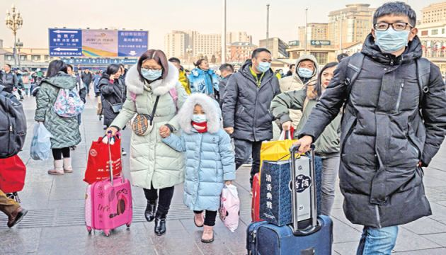 People wearing protective masks arrive at Beijing railway station to head home for the Lunar New Year on Tuesday.  China has confirmed human-to-human transmission in the outbreak of a new SARS-like virus as the number of cases soared.- AFP