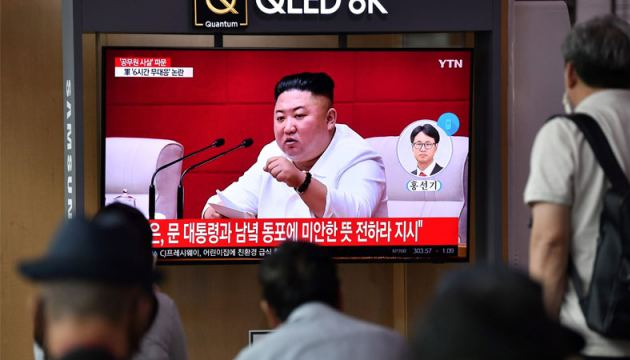 People watch a television news broadcast showing file footage of North Korean leader Kim Jong Un, at a railway station in Seoul on Friday. Kim  apologised over the killing of a South Korean at sea.- AFP