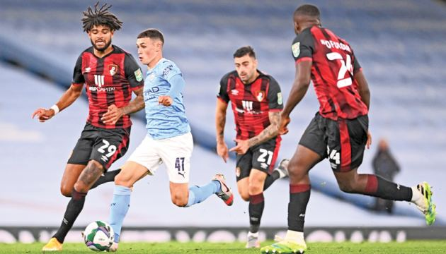 Manchester City's English midfielder Phil Foden (2nd L) runs through the Bournemouth midfield during the English League Cup third round football match between Manchester City and Bournemouth at the Etihad Stadium in Manchester.