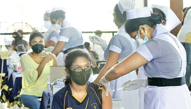 The vaccination of 18-19 year olds against COVID-19 commenced at several Colombo schools yesterday. Here a student of Visakha Vidyalaya gets inoculated at her school. (Picture by Dushmantha Mayadunne)