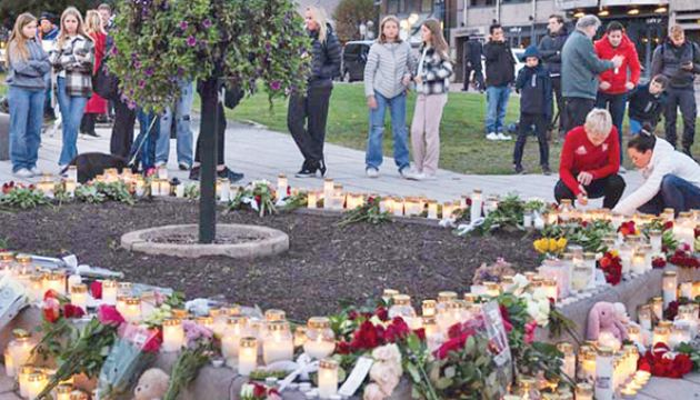 People gather at a makeshift memorial in Kongsberg, Norway on Thursday, to victims of a bow-and-arrow attack a day earlier.