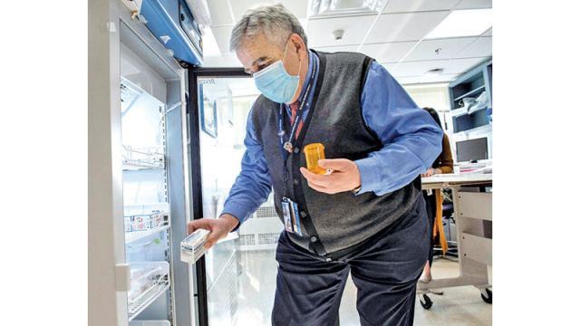 Pharmacist Antoun Houranieh unlocks a refrigerator and takes out a box of the Johnson & Johnson COVID -19 Janssen Vaccine to be used for the day's at home vaccinations at the US Department of Veterans Affairs' VA Boston Healthcare System's Jamaica Plain Medical Center in Boston, Massachusetts on Thursday. - AFP