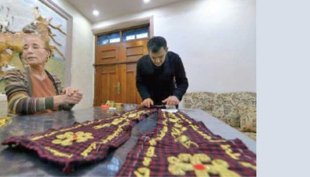 Karjiya Baqtar who has worked with other Iraqi Christians for two months on the shawl to be presented to Pope Francis on his visit to the town is seen with Iraqi priest Ammar Yaqo who designed the fabric.