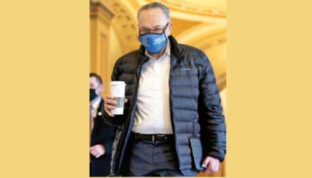 Senate Majority Leader Charles E. Schumer, a Democrat from New York wears a protective mask while arriving to the U.S. Capitol in Washington, D.C., on Thursday for the debate.