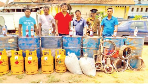 The Police Officers along with the items used for distilling illegal liquor.