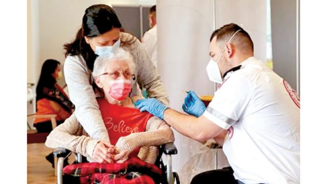 An elderly woman receives a booster shot of her vaccination against COVID-19 at an assisted living facility, in Netanya, Israel.