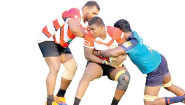 Pulasthi Dassanayake (centre) being held by an Air Force defender in a club rugby match.