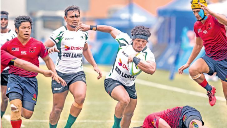 Sri Lanka Sevens skipper Sudarshana Muthuthanthri making a break in the match against Malaysia with Hirantha Perera in support. Picture courtesy:  Sameera Peiris
