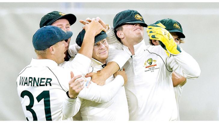 Australia's Steve Smith (3rd-L) is mobbed by his teammates after catching New Zealand captain Kane Williamson  on day two of the first Test cricket match between Australia and New Zealand in Perth on December 13. -AFP