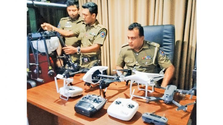 Dehiwala Police officers with the seized drone cameras.  Picture by S.Kahatapitiya.