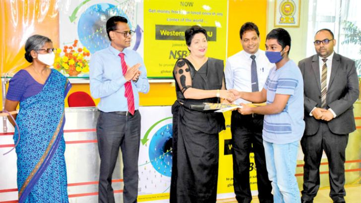 Keasila Jayawardana handing over a receipt after the first transaction. Also present are Ajith Pieris, Western Union Sri Lanka Channel Manager Praveen Nanayakkara and other officials. Picture by Saliya Rupasinghe.