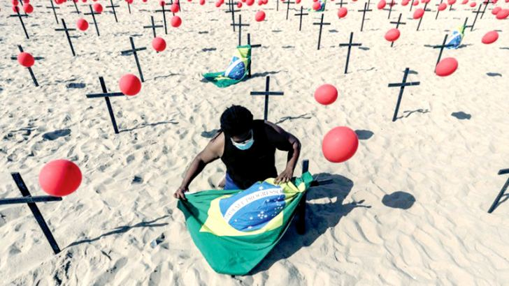 An activist ties a Brazilian national flag along with red balloons and crosses at Copacabana beach in Rio de Janeiro, Brazil honouring victims of the Coronavirus pandemic.