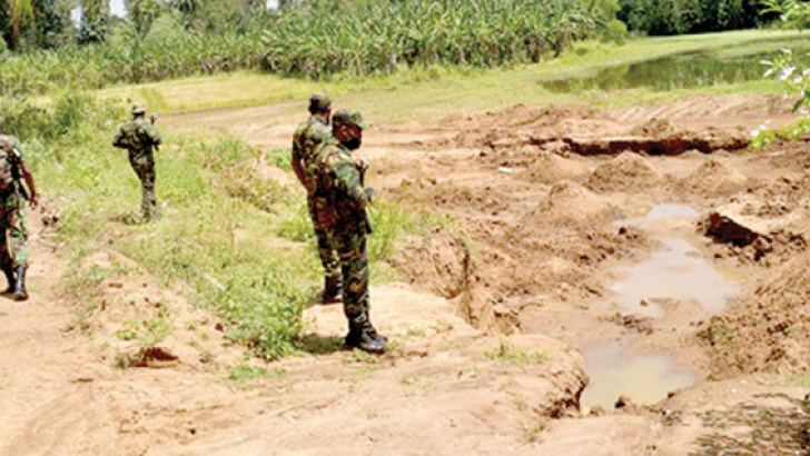 Police Officers inspecting a sand mining area during the raid.