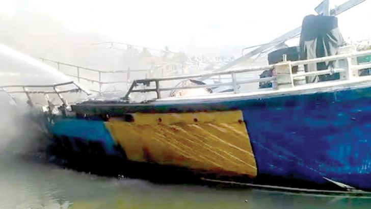 The fire on the trawler being doused. Picture by Mihira Wijesekara, Marawila Group Corr.