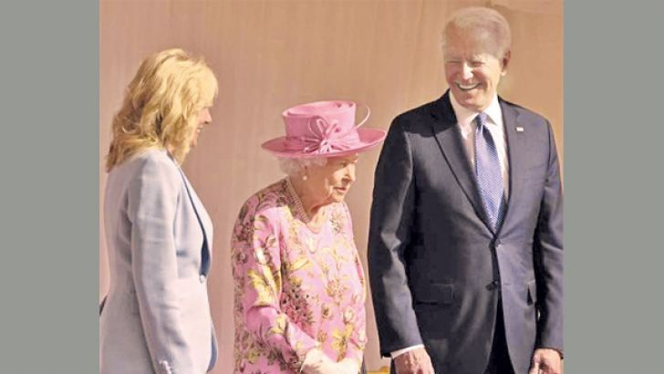 US President Joe Biden and First Lady Jill Biden standing with Queen Elizabeth II watching a Guard of Honour march past before their meeting at Windsor Castle.