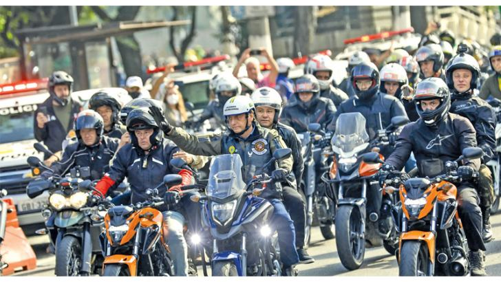 Brazil's President Jair Bolsonaro,(c), waves as he leads a caravan of motorcycle enthusiasts following him through the streets of the city in Sao Paulo, Brazil on June 12, 2021.