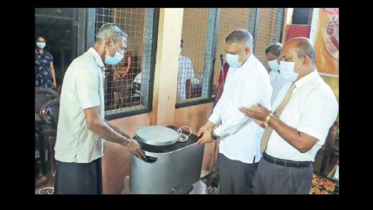 State Minister Kanaka Herath handing a pottery making machinery over to a beneficiary.