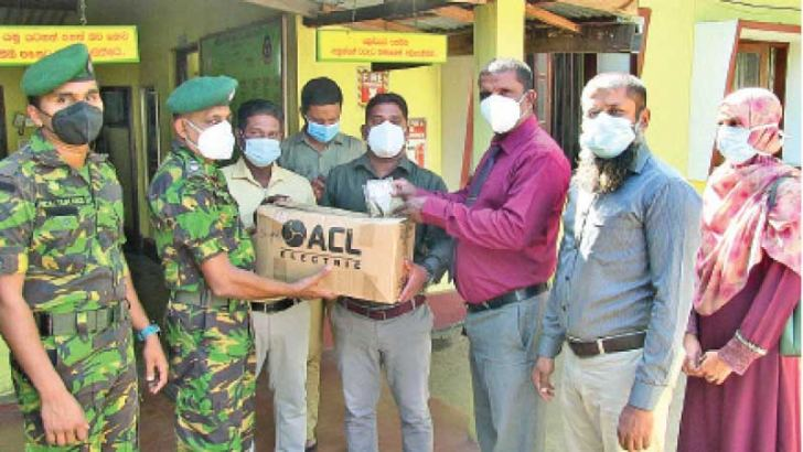 Periyaneelavanai STF Acting In-charge S.M.P.P.M. Dais receiving a pack of native medicinal drinks.