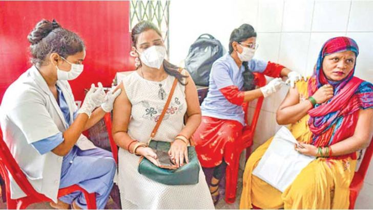 Health workers inoculate women at a COVID-19 vaccination center in New Delhi.