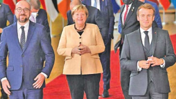 From left: European Council President Charles Michel, German Chancellor Angela Merkel and French President Emmanuel Macron prepare to take a photo together in Brussels, Belgium on Sunday.